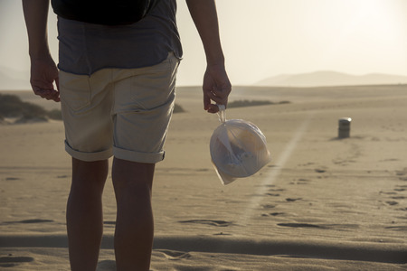 closeup of a young backpacker man wearing shorts seen from behind carrying a transparent plastic bag with leftovers as he walks by the sand