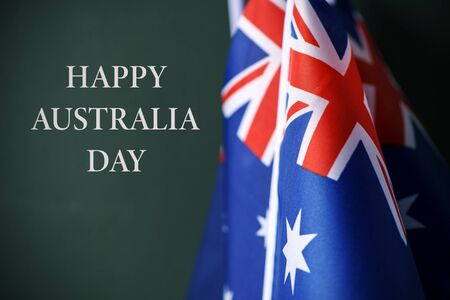closeup of some australian flags and the text happy australia day against a dark green background Banque d'images