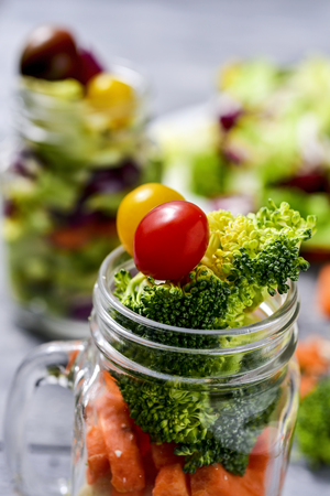 a salad with a mix of different vegetables, such as cauliflower, carrot, broccoli and cherry tomatoes of different colors served in a mason jar, on a gray rustic wooden table