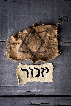 high angle view of a ragged jewish badge and a yellowish piece of paper with the word yizkor, remember in hebrew and the name of a prayer in memory of deceased beloveds, on a rustic wooden surface