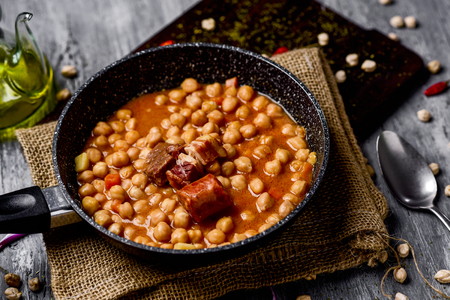 a stone frypan with garbanzos a la riojana, a spanish chickpeas stew, on a wooden chopping board placed on a rustic wooden table next to a cruet with olive oil