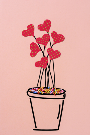a drawing of a plant in a plant pot with some hearts cut out of a red papper patterned with green dots simulating flowers, on a pale pink background