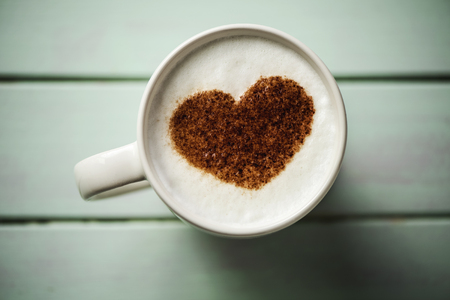 high-angle shot of a white ceramic cup of cappuccino with a heart drawn with cocoa powder on its milk foam, on a pale green rustic wooden table