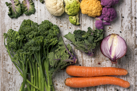 high angle shot of some different raw vegetables, such as cauliflower of different colors, broccolini, fava beans, french beans, kale, onion or carrots, on a white rustic wooden table  Stock Photo