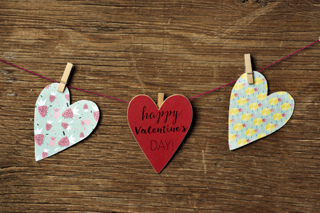 Some hearts hung with clothespins in a clothes line and a red heart-shaped signboard with the text happy valentines day written in it, against a rustic wooden background Stock fotó
