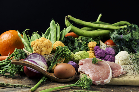 a pile of some fruit and some different raw vegetables, such as cauliflower of different colors, broccolini or french beans, and some eggs and some slices of meat on a rustic wooden table Stockfoto