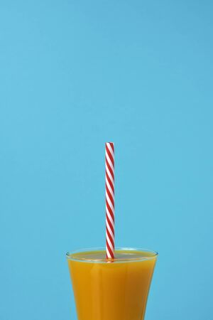 an orange beverage served in a glass with a red and white drawing straw, on a blue background with some blank space on top