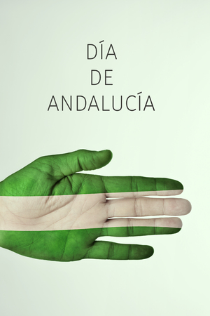 the text Dia de Andalucia, Day of Andalusia in Spanish, and the hand of a young man patterned with the flag of Andalusia, against a pale green background