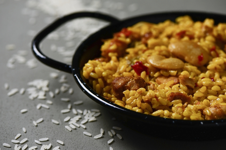 closeup of a typical spanish paella valenciana in a typical paella pan, on a gray rustic surface Фото со стока