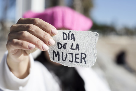 closeup of a young woman outdoors wearing a pink hat showing a piece of paper in front of her face with the text dia de la mujer, womens day written in spanish