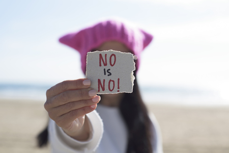 closeup of a young caucasian woman outdoors wearing a pink hat showing a piece of paper in front of her face with the text no is no written in it Foto de archivo