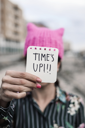 closeup of a young caucasian woman outdoors wearing a pink  hat showing a piece of paper in front of her face with the text time is up written in it