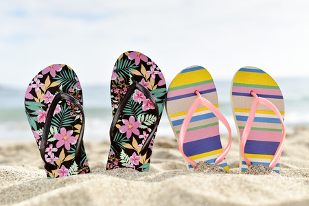closeup of two different pairs of colorful flip-flops, one of them flower-patterned and the other striped, stuck on the sand of a quiet beach, with some blank space on top Stock Photo