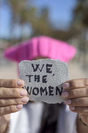 closeup of a young caucasian woman outdoors wearing a pink  hat showing a piece of paper in front of her face with the text we the women written in it