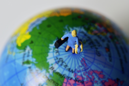 miniature traveler woman seen from above carrying some suitcases, on the top of a terrestrial globe