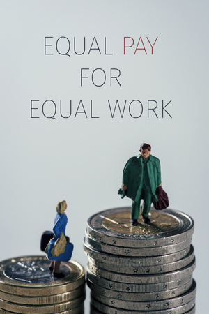 a miniature woman and a miniature man on the top of two different piles of euro coins, the man on the highest pile and the woman on the shortest pile, and the text equal pay for equal work