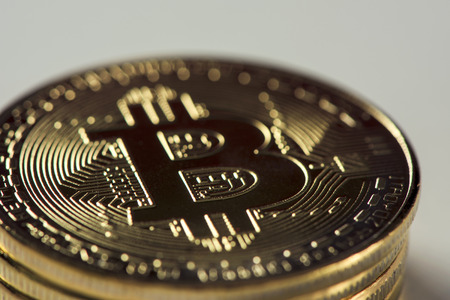 closeup of a pile of bitcoins against an off-white background