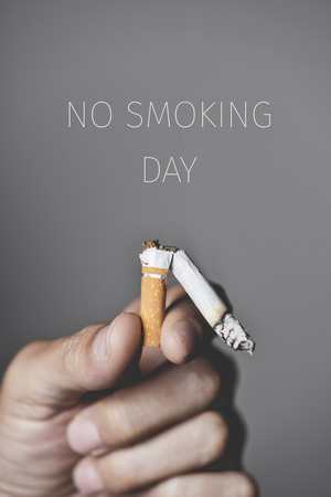 closeup of a young caucasian man with a broken lit cigarette in his hand and the text no smoking day Banque d'images