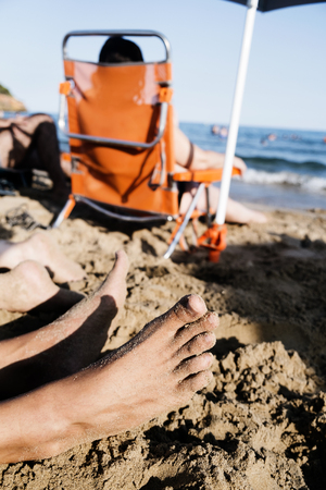 closeup of the feet of two young caucasian men lying down on the sand of a beach, and some unrecognizable people relaxing in deck chairs in the background