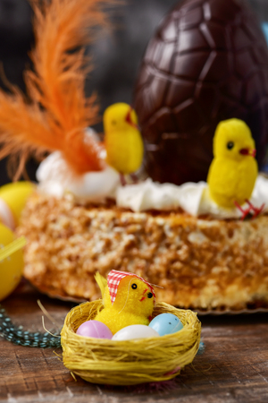 a toy chick and some eggs in a nest, and a mona de pascua, a cake eaten in Spain on Easter Monday, topped with a chocolate egg, some feathers and some toy chicks, placed on a rustic wooden table Foto de archivo