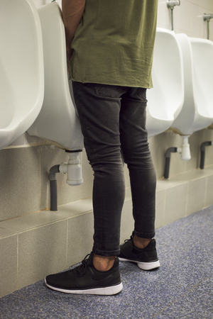 closeup of a young caucasian man seen from behind using a urinal in a public washroom