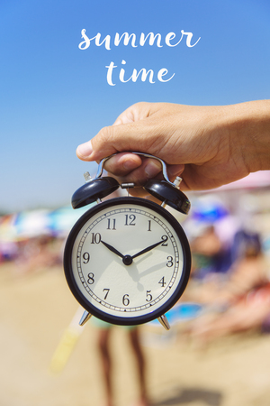 closeup of a young caucasian man with an alarm clock in his hand on the beach, next to the seashore and the text summer time on top
