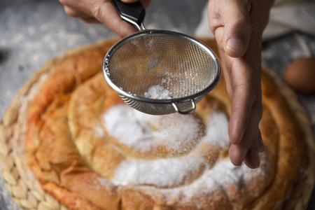 Close-up van een jonge blanke man die poedersuiker op een ensaimada, een typisch gebakje van Mallorca, Spanje, op een rustieke houten tafel strooit Stockfoto - 97242725