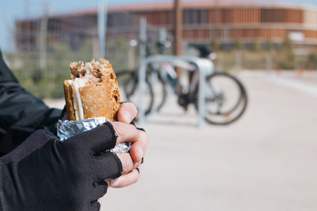 closeup of a young caucasian cyclist man wearing cycling gloves eating a ham and cheese sandwich, wrapped in aluminum foil, next to his bicycle outdoors Reklamní fotografie