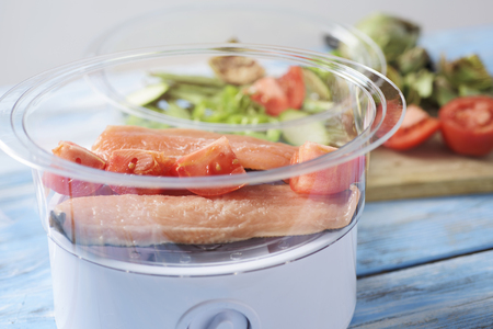 some raw fillets of trout and some slices of tomato in an electric steam cooker, on a pale blue wooden table and some raw vegetables in the background, such as green beans, artichoke or tomato Stock Photo