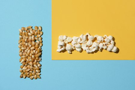 high angle view of a pile of unpopped corn and a pile of popcorn arranged in two perpendicular lines on a colorful yellow and blue background, with some blank space around them