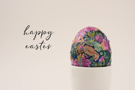 closeup of a homemade decorated easter egg in a white ceramic egg-cup and the text happy easter against an off-white background