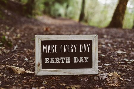 closeup of a wooden-framed chalkboard with the text make every day earth day written in it, on the ground in the woods