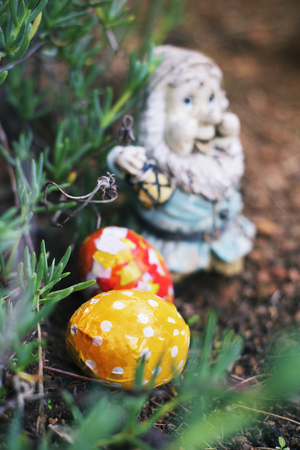 closeup of some homemade decorated easter eggs, made by myself, hidden in the garden next to an old and weathered garden gnome Stock Photo