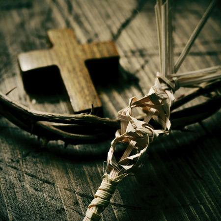 closeup of a small traditional spanish braided palm leaf to be blessed on Palm Sunday, a small wooden cross and a depiction of the crown of thorns of Jesus Christ on a wooden surface