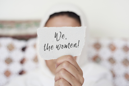 closeup of a young woman indoors wearing a white hijab showing a piece of paper in front of her face with the text we the women written in it Stock Photo