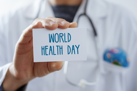 closeup of a young caucasian doctor man, with a world globe in the pocket of his white coat, showing a signboard with the text world health day written in it Stock Photo