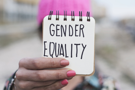 closeup of a young woman outdoors wearing a pink pussycat hat showing a notepad in front of her face with the text gender equality written in it