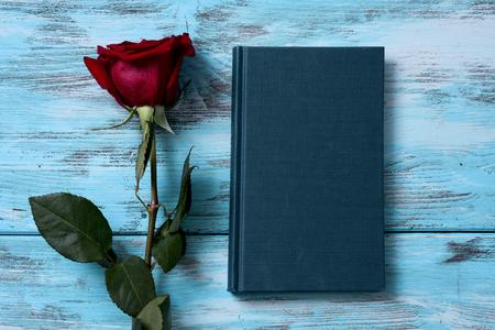 Vista de ángulo alto de una rosa roja y un libro para Sant Jordi, el nombre catalán para el Día de San Jorge, cuando es tradición regalar rosas rojas y libros en Cataluña, España