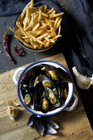 moules-frites, mussels and fries typical of Belgium, on a rustic wooden table Imagens - 98825310