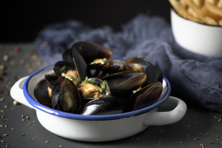 moules-frites, mussels and fries typical of Belgium, on a rustic wooden table