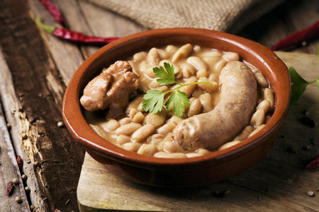 closeup of an earthenware bowl with a cassoulet de Castelnaudary, a typical bean stew from Occitanie, in France, on a rustic wooden table Stockfoto