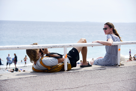 NICE, FRANCE - JUNE 4, 2017: A young tourist man takes a picture of his partner at the famous Promenade des Anglais bordering the Mediterranean sea in Nice, in the French Riviera, France Editorial