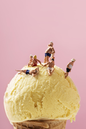 some miniature people wearing swimsuit relaxing on an ice cream ball, against a pink background with some blank space on top