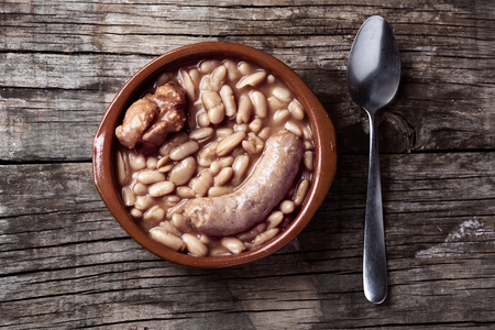 high angle view of an earthenware bowl with a cassoulet de Castelnaudary, a typical bean stew from Occitanie, in France, on a rustic wooden table