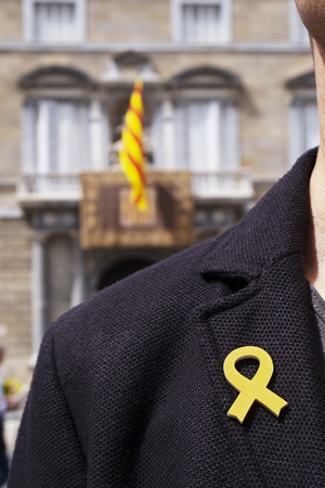 young man with a yellow ribbon pinned in the flap of his jacket in front of the Palau de la Generalitat de Catalunya, the seat of the Government of Catalonia in Barcelona, Spain