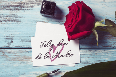 a red rose, an ink bottle, a nib pen and a piece of paper with the text feliz dia de la madre, happy mothers day written in spanish, on a blue rustic wooden table Stock Photo