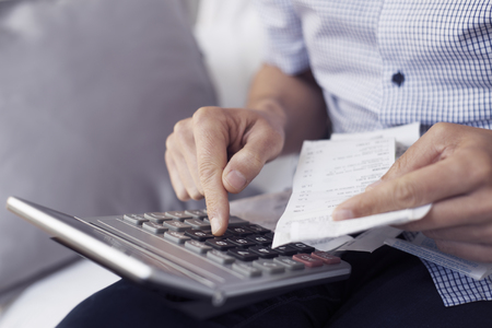 closeup of a young caucasian man with a pile of bills and tickets in his hand using an electronic calculator to do some accounts