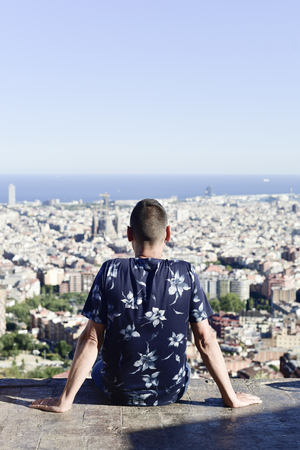 closeup of a young caucasian man, seen from behind, at the top of a hill observing the city of Barcelona, Spain, below him