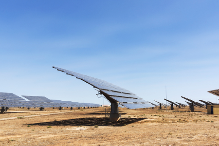 a view of some solar panels in a solar power plant, in a desert landscape