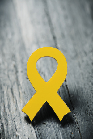 closeup of a yellow ribbon on a gray rustic wooden surface, with some blank space on top Stock Photo